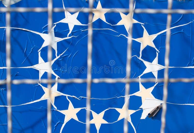 Bandeira rasgada da União Europeia através da cerca de fio fotos de stock