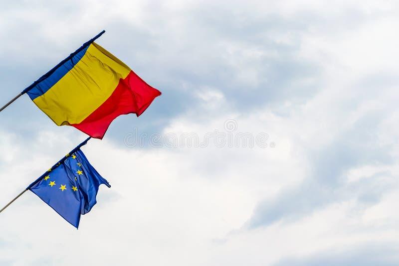 Bandeira romena e bandeira da União Europeia que acena em ventos fortes, com as nuvens tormentosos no fundo, em Sibiu, Romênia -  imagem de stock