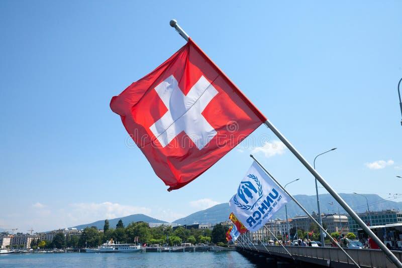 A bandeira suíça e as bandeiras do UNHCR aproximam o lago do leman em Genebra O UNHCR é a agência dos United Nations responsável  imagens de stock