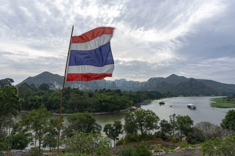 A bandeira tailandesa fundida do vento, o fundo é a vista do rio Kwai e das montanhas de Kanchanaburi, Tailândia fotos de stock royalty free