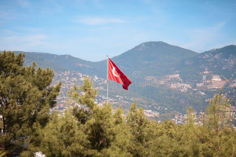 Bandeira turca de voo em um fundo das montanhas perto da cidade de Alania fotografia de stock royalty free