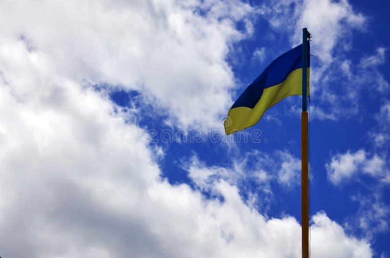 Bandeira ucraniana contra o céu azul com nuvens A bandeira oficial do estado ucraniano inclui a cor amarela e azul imagem de stock