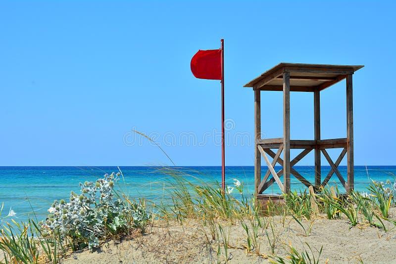 A bandeira vermelha e a casa da salva-vidas imagens de stock
