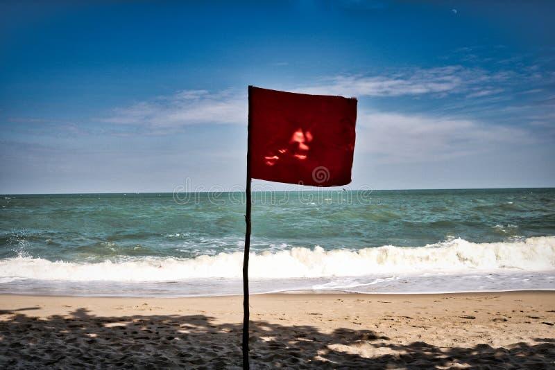 Bandeira vermelha em uma praia fotografia de stock royalty free