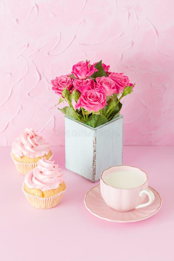 Bandeira vertical pastel cor-de-rosa com queques decorados, copo do coffe com leite e ramalhete de rosas cor-de-rosa imagem de stock