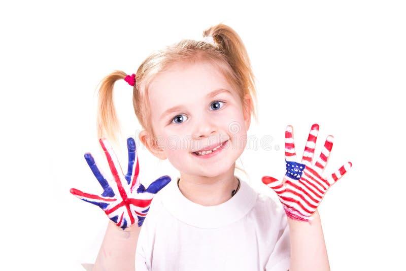 Bandeiras americanas e inglesas nas mãos da criança. foto de stock royalty free