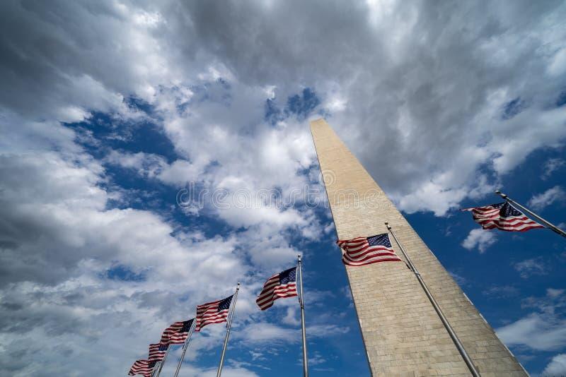 Bandeiras americanas que fundem no vento com Washington Monument ao longo do National Mall C?u em parte nebuloso fotos de stock