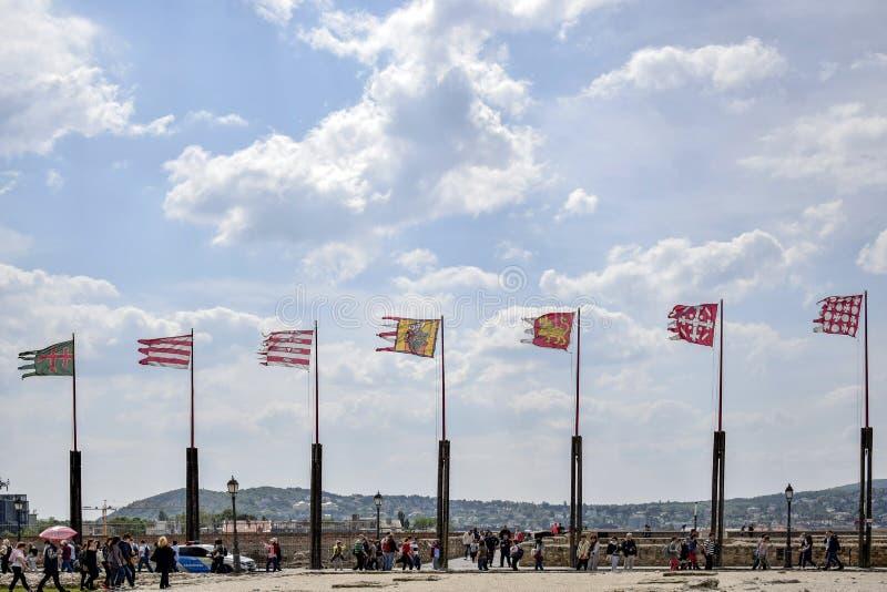 Bandeiras antigas que vibram no vento no fundo do céu nebuloso azul fotografia de stock
