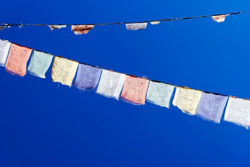 Bandeiras budistas da oração com fundo do céu azul foto de stock