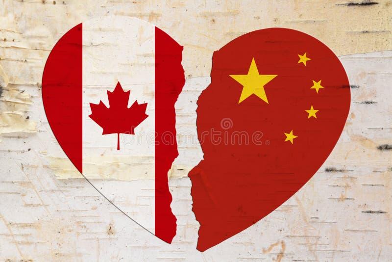 Bandeiras canadenses e chinesas em um coração quebrado fotografia de stock