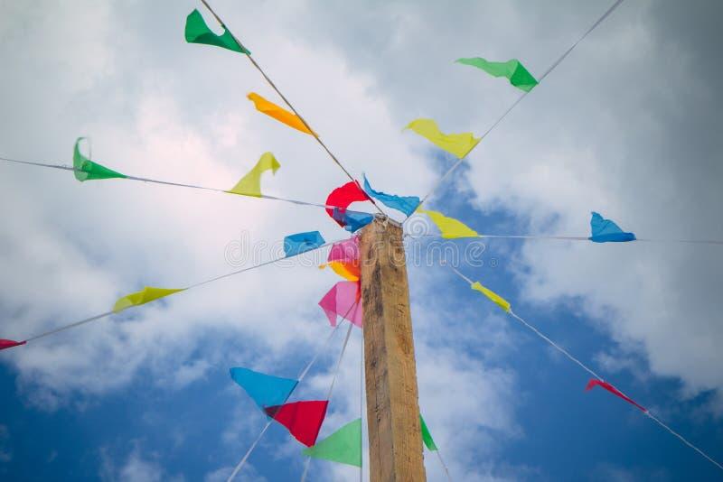 Bandeiras coloridas da decoração contra o fundo do céu azul em crianças de jogo felizes e alegres de um festival do verão, jogos  fotos de stock royalty free