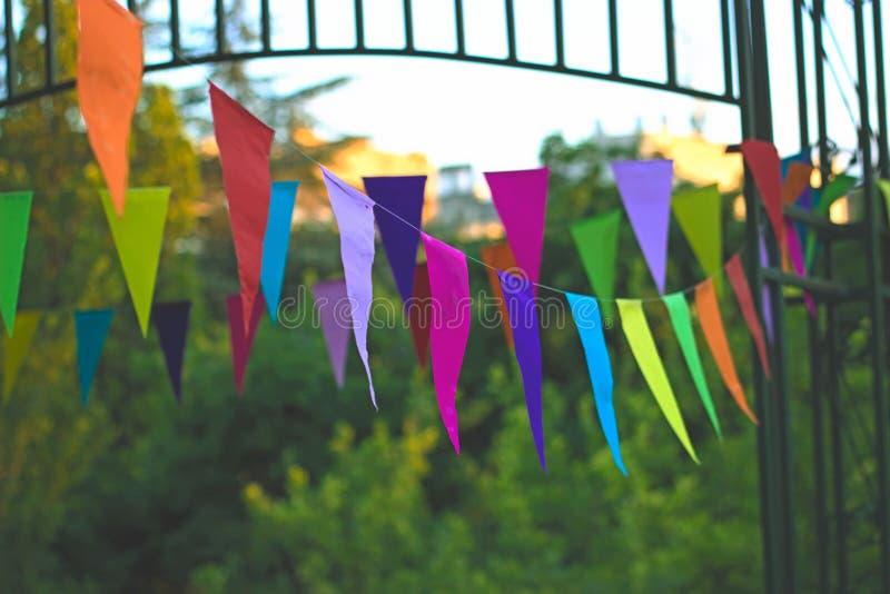 Bandeiras coloridas do aniversário que penduram no quintal imagens de stock royalty free