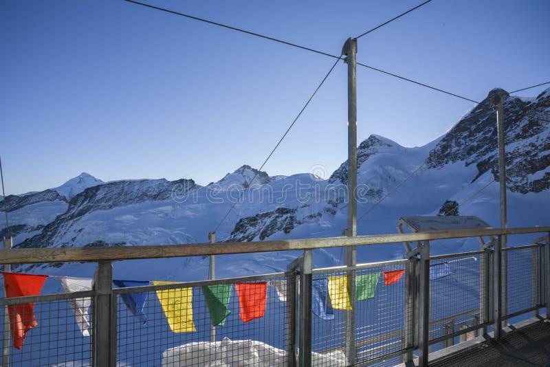 Bandeiras coloridas na torre de observação da esfinge na cordilheira Neve-tampada em Jungfraujoch, Suíça, Europa fotografia de stock royalty free