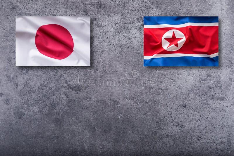 Bandeiras da Coreia do Norte e do Japão Bandeira da Coreia do Norte e do Japão no concr imagens de stock royalty free