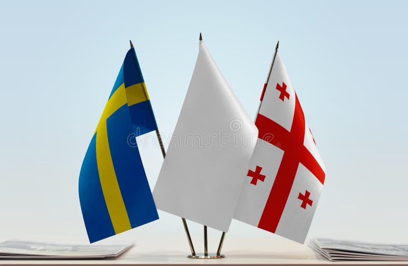 Bandeiras da Suécia e do Geórgia imagens de stock royalty free