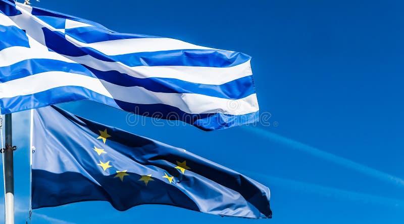 Bandeiras de Gr?cia e da Uni?o Europeia no fundo do c?u azul, pol?tica de Europa fotografia de stock