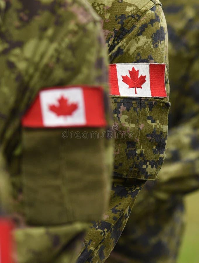 Bandeiras do remendo de Canadá no braço dos soldados Tropas canadenses imagem de stock