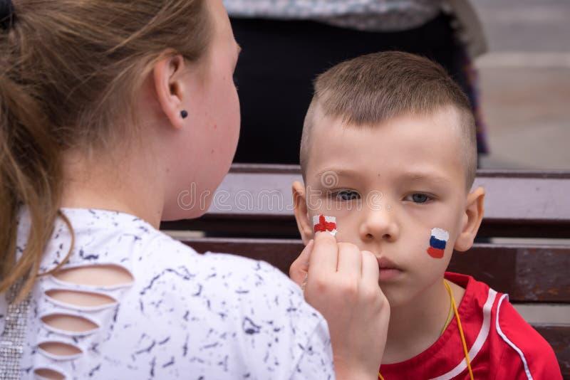 Bandeiras do russo e do inglês do desenho da mulher nos mordentes do aficionado desportivo novo do menino imagens de stock