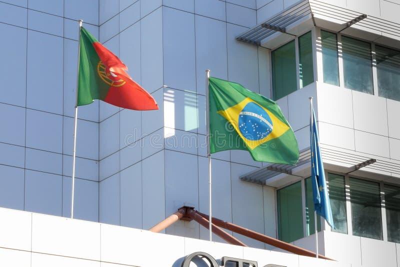 Bandeiras portuguesas e brasileiras que voam de lado a lado em uma construção em Porto, Portugal foto de stock