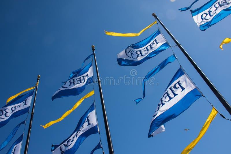 Bandeiras que comemoram a mosca do aniversário do cais 39's 39th contra um céu azul imagens de stock