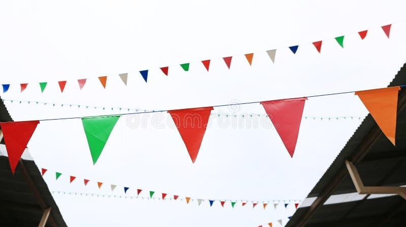 Bandeiras triangulares coloridos que penduram entre a casa velha do vintage fotografia de stock royalty free
