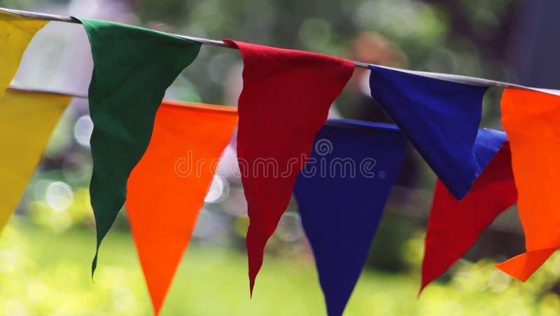 Bandeiras triangulares das flâmulas listradas coloridos decorativas do partido em uns dois corda, close up fotografia de stock