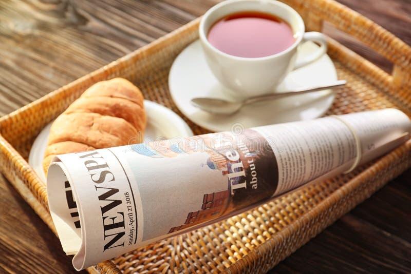 Bandeja com jornal e copo do chá no fundo de madeira fotografia de stock