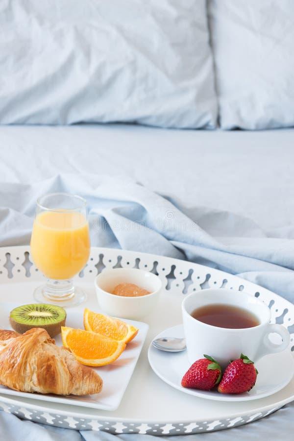 Bandeja com pequeno almoço saboroso em uma cama imagens de stock