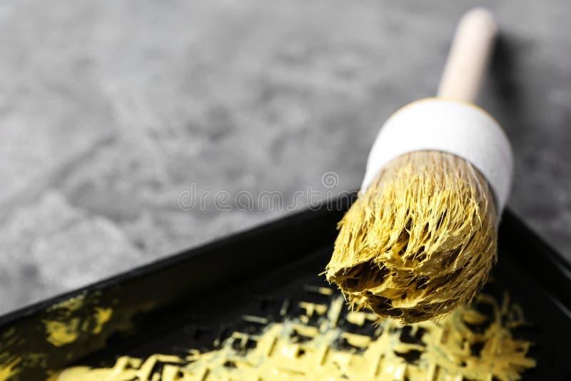 Bandeja com pintura e escova para a decoração interior no fundo cinzento, close up fotografia de stock