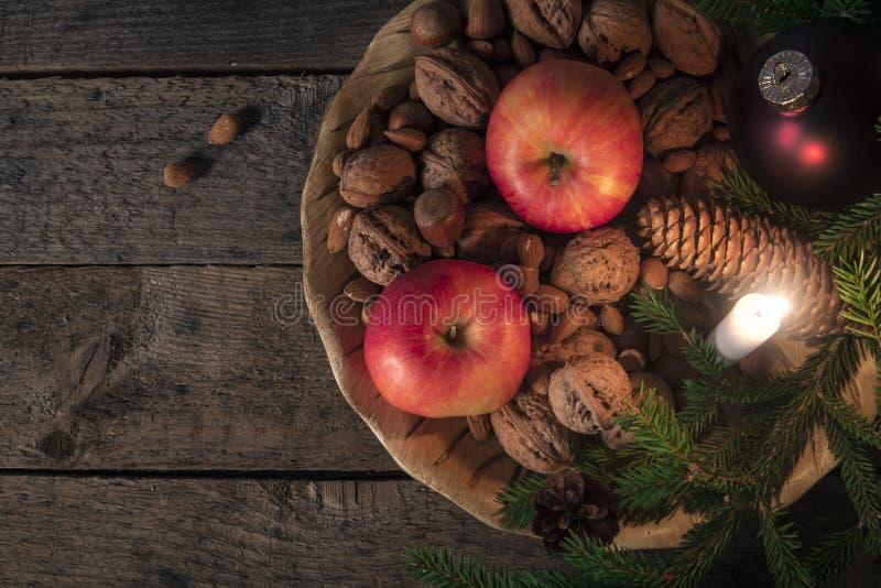 Bandeja com porcas e maçãs com decoração do Xmas imagens de stock royalty free