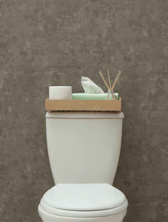 Bandeja com rolo de papel, de guardanapo e do refrogerador de ar de lingüeta no tanque do toalete perto da parede cinzenta foto de stock