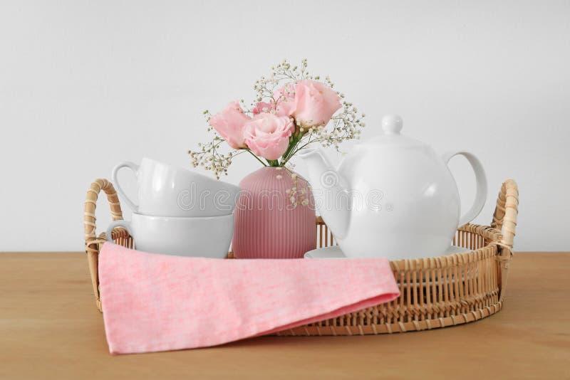 Bandeja con el juego de té y ramo hermoso en la tabla de madera fotografía de archivo libre de regalías