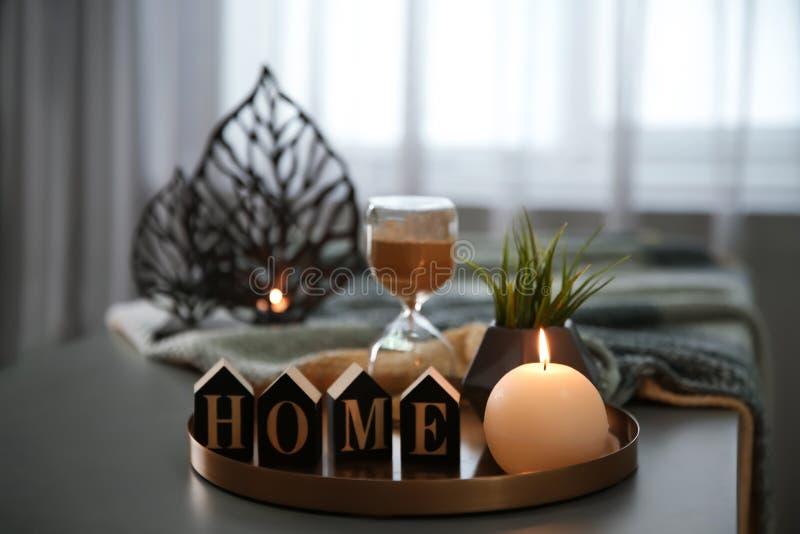 Bandeja con la vela, la palabra HOGAR y el reloj de arena ardientes foto de archivo