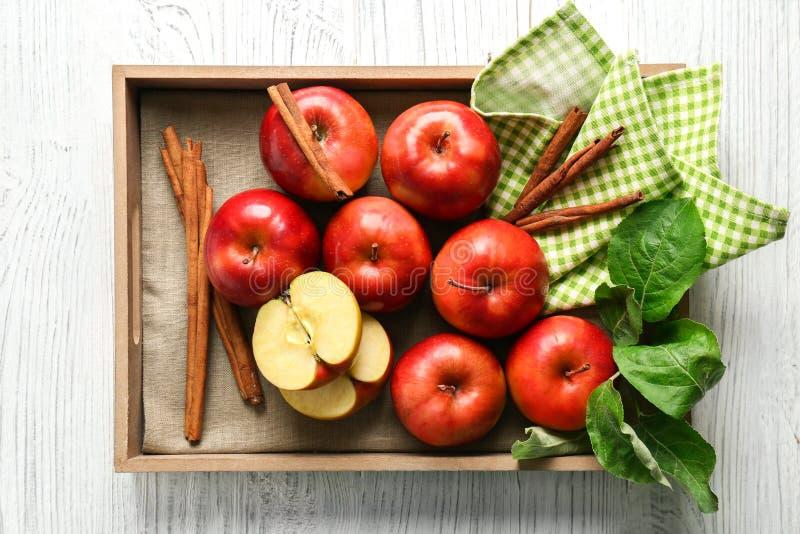 Bandeja con las manzanas y los palillos de canela foto de archivo libre de regalías
