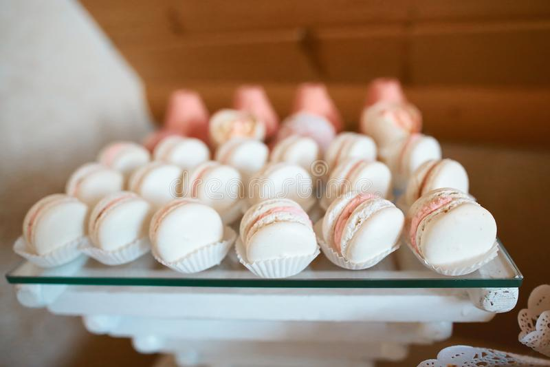 Bandeja con las tortas y los macarrones deliciosos Macarrones coloridos Tabla dulce elegante con la torta grande, las magdalenas, imagen de archivo libre de regalías