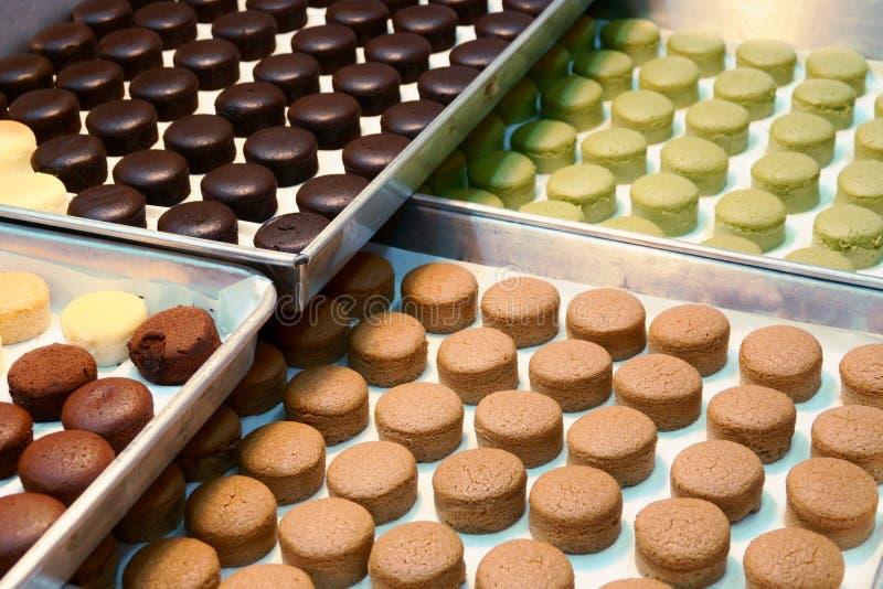 Bandeja con los macarrones frescos de las tortas en la tienda de la panadería foto de archivo