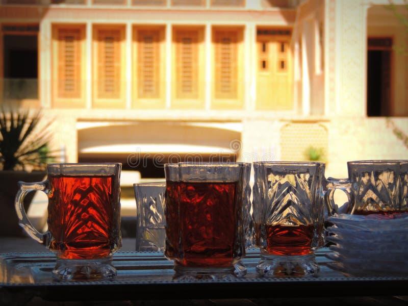 Bandeja con los vidrios del té por la fachada tradicional de la arquitectura fotos de archivo libres de regalías