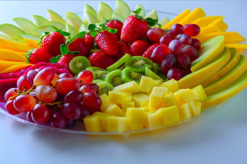 Bandeja crua da variedade dos frutos na placa branca, na tabela branca fotos de stock royalty free