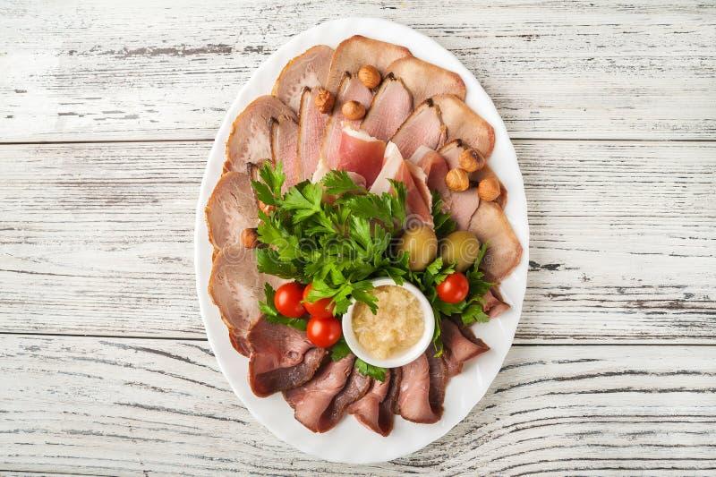 Bandeja da carne em um close-up branco da placa Presunto cozido, presunto espanhol, carne assada, espaço fumado da cópia do peito fotografia de stock
