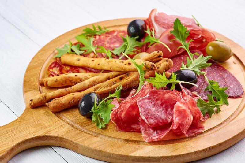 Bandeja da carne no tampo da mesa de madeira branco com grissini, prosciutto, salame, salsicha, e azeitonas imagem de stock