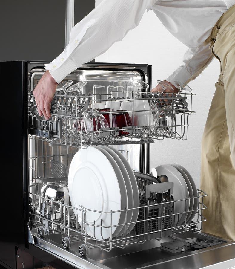 Bandeja da máquina de lavar louça que guarda pelo homem imagens de stock