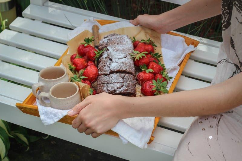 Bandeja da terra arrendada da jovem mulher com um bolo caseiro e umas morangos frescas imagens de stock royalty free