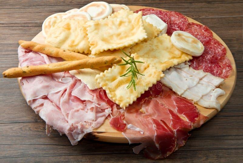 Bandeja de carnes curadas, de queijos e de bolinho de massa fritado imagens de stock
