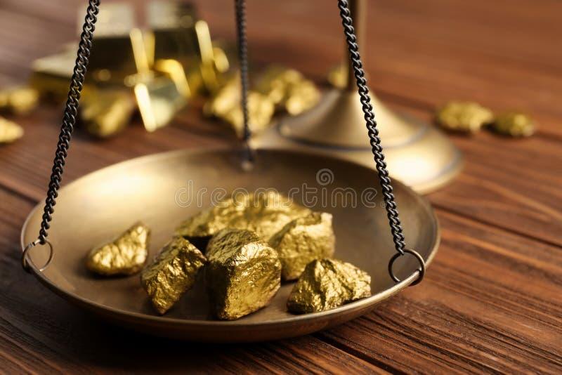 Bandeja de escala com as protuberâncias do ouro na tabela de madeira imagens de stock
