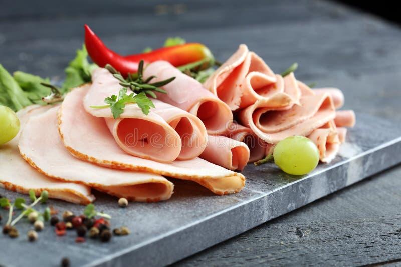 Bandeja de la comida con el salami delicioso, los pedazos de jamón cortado, la salchicha, los tomates, la ensalada y la verdura - imagen de archivo libre de regalías