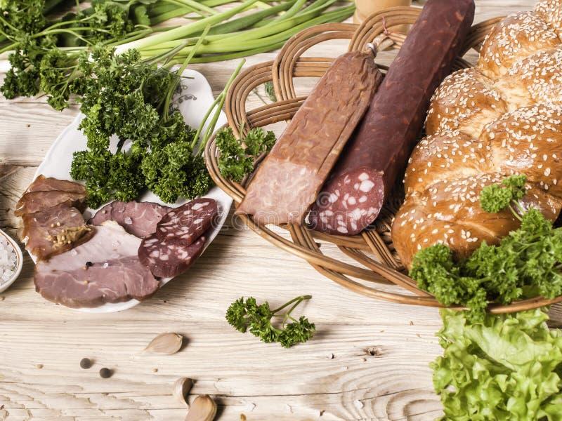 Bandeja de la comida con el salami delicioso, los pedazos de jamón cortado, la salchicha, los tomates, la ensalada y la verdura - fotos de archivo