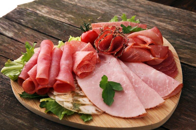 Bandeja de la comida con el salami delicioso, los pedazos de jamón cortado, la salchicha, los tomates, la ensalada y la verdura - fotos de archivo libres de regalías
