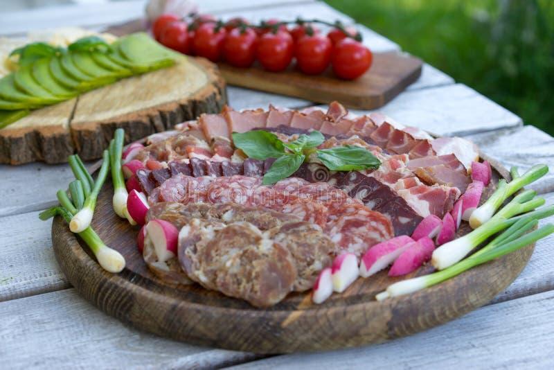 Bandeja de la comida con el salami delicioso, los pedazos de jamón cortado, la salchicha, los tomates, la ensalada y la verdura - fotografía de archivo libre de regalías