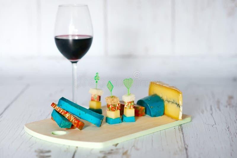 Bandeja de la copa de vino y de madera con quesos foto de archivo