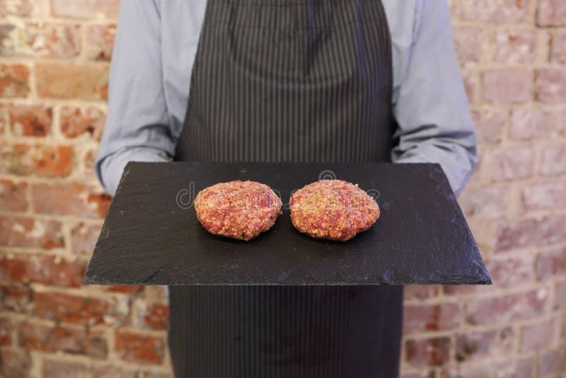 Bandeja de la tenencia del hombre con 2 hamburguesas encendido fotografía de archivo